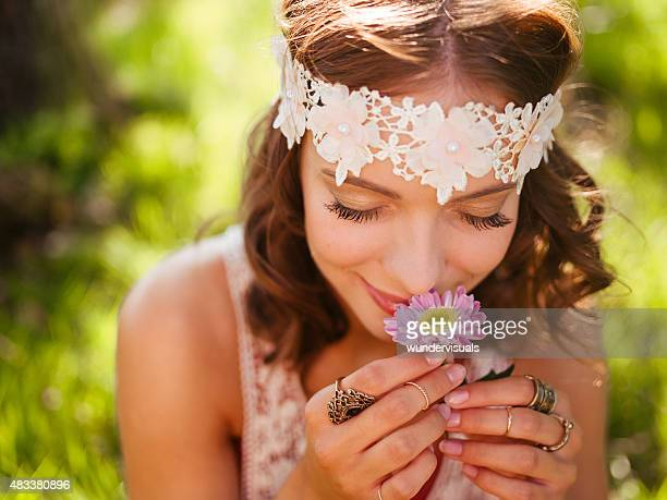 Girl in boho style smelling a fresh flower in nature