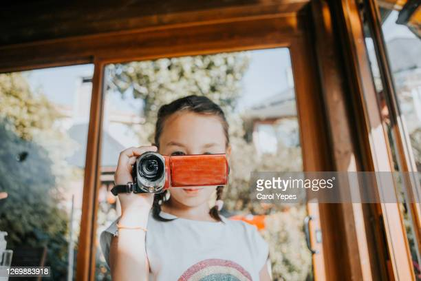 girl (10) in braids filming with video camera to her family during summer day - ルポルタージュ ストックフォトと画像