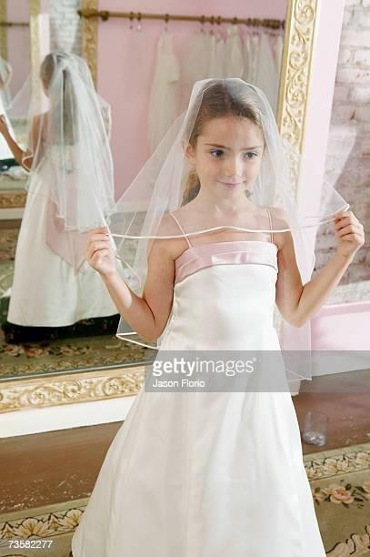 Girl (7-8) in bridal shop holding veil, portrait