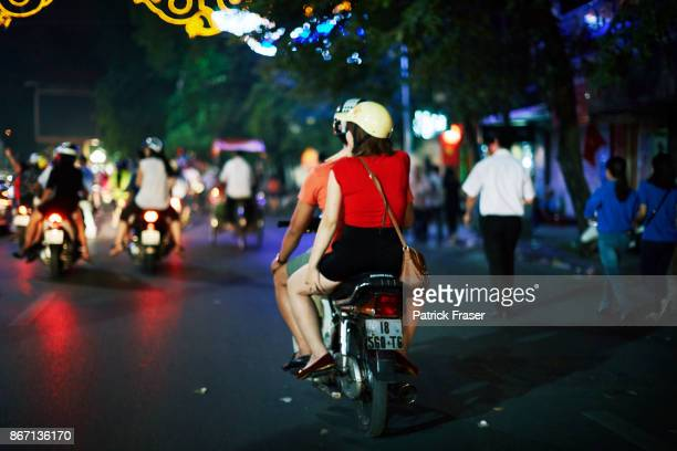Girl in bright red shirt rides motorcycle with boy at night in city