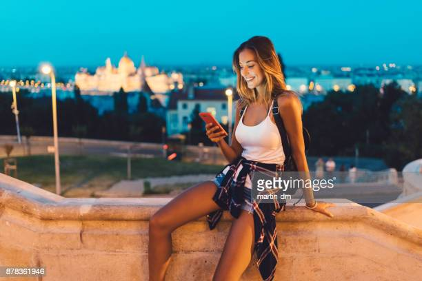 Girl in Budapest texting at twilight