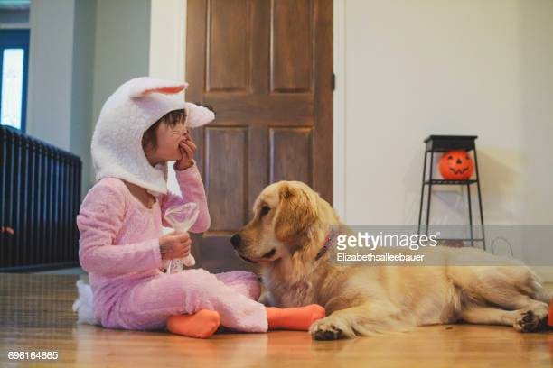girl in bunny costume sitting on floor eating halloween candy with golden retriever dog - dog eats out girl stock pictures, royalty-free photos & images