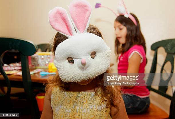 Girl in Bunny Mask with Older Sister in Backgro