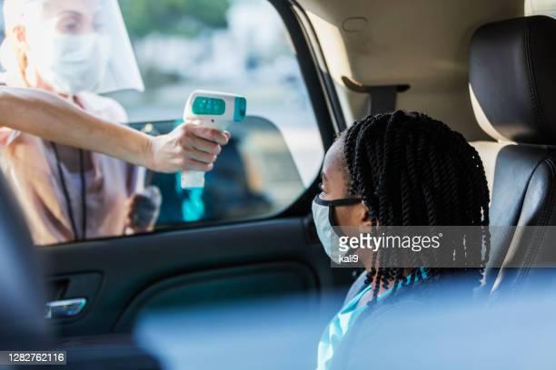 居心地の良い-19温度チェックポイントで車の中の女の子 - ドライブスルー検査 ストックフォトと画像