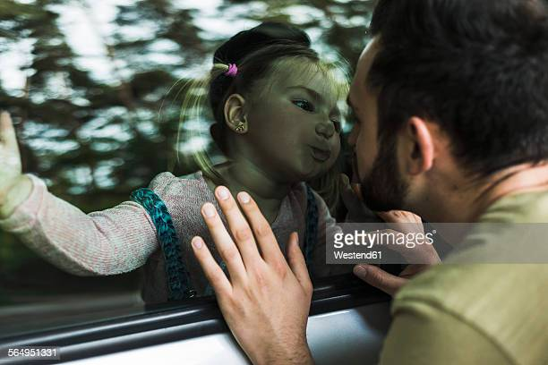 Girl in car kissing father behind window pane