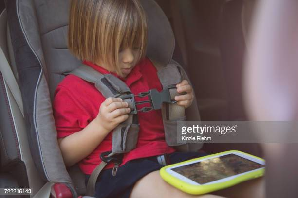 Girl in car safety seat fastening her seat belt
