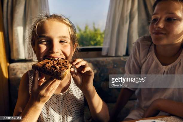 girl in caravan watching her sister eating a toast with chocolate spread - essen mund benutzen stock-fotos und bilder