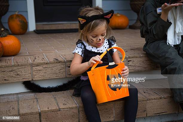 girl in cat costume peering into trick or treating bag on porch stairway - cat costume stock photos and pictures