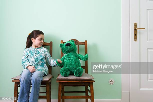 Girl in Chair Holding Hands with Green Teddy Bear