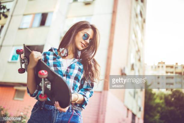 Girl in checkered shirt with skateboard