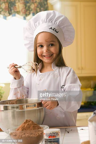 Girl (4-5) in chef outfit holding up whisk covered with batter, smiling, portrait
