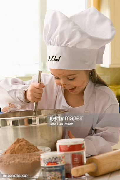 Girl (4-5) in chef outfit mixing batter, smiling