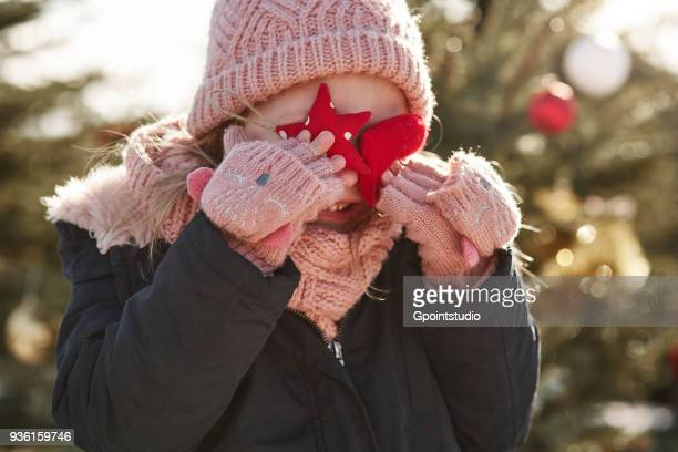 Girl in christmas tree forest covering her eyes with christmas decorations