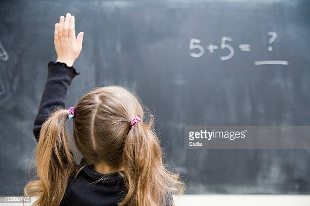 Girl in classroom with raised hand