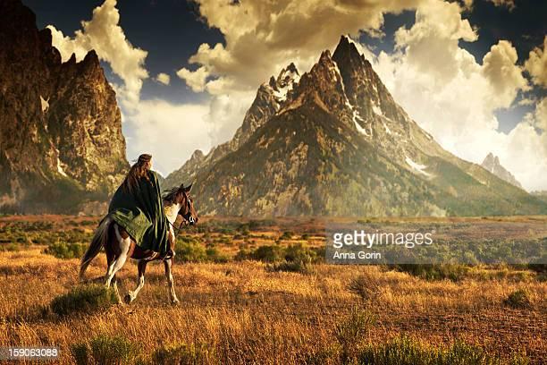 Girl in cloak rides horse toward tall mountains