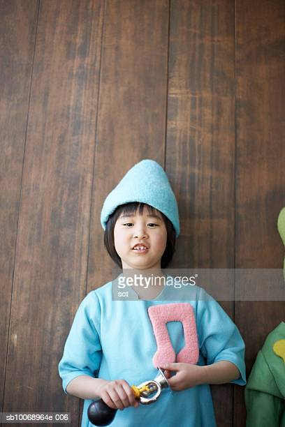 Girl (8-9) in colorful costume, holding toy musical instrument, portrait
