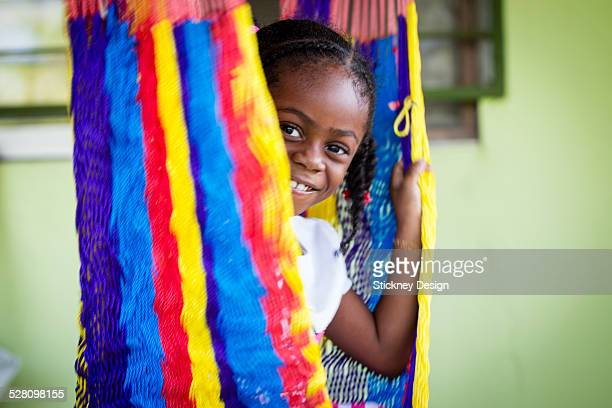Girl in colorful hammock chair in outdoor porch