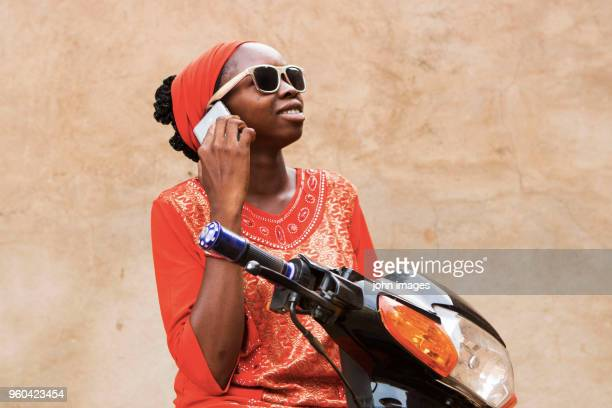 a girl in communication on the bike - mali photos et images de collection