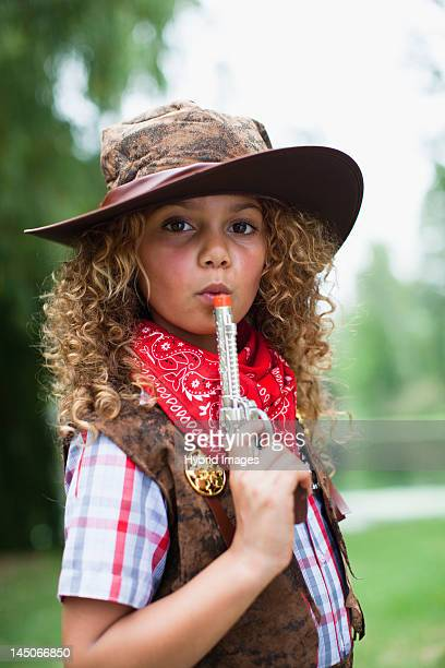 Girl in cowboy hat with toy pistol