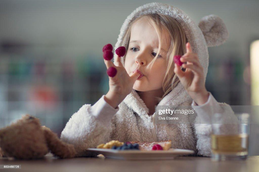 Girl in cozy hooded pyjamas, eating raspberries off her fingers : Stock-Foto