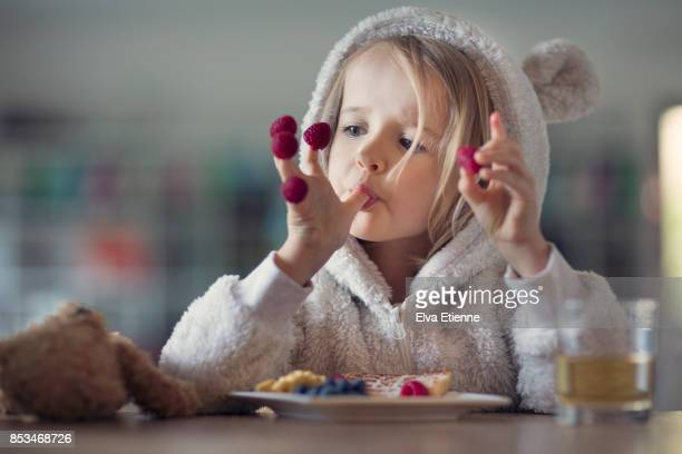 girl in cozy hooded pyjamas, eating raspberries off her fingers - kindheit stock-fotos und bilder