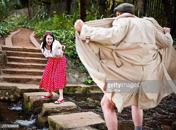 girl in cute outfit laughs at raincoat clad flasher - male flashers stock photos and pictures