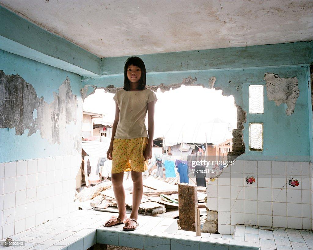 Girl in damaged kitchen following typhoon : Stock Photo