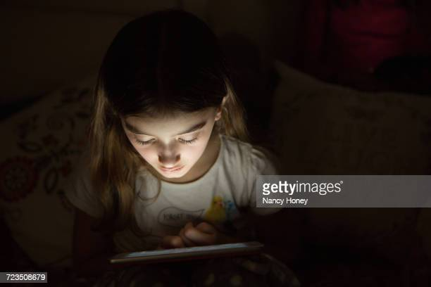 girl in darkness illuminated by light from digital tablet - vulnerability stock pictures, royalty-free photos & images