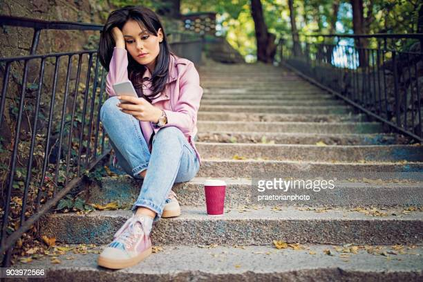 Girl in depression is standing sad on the stairs