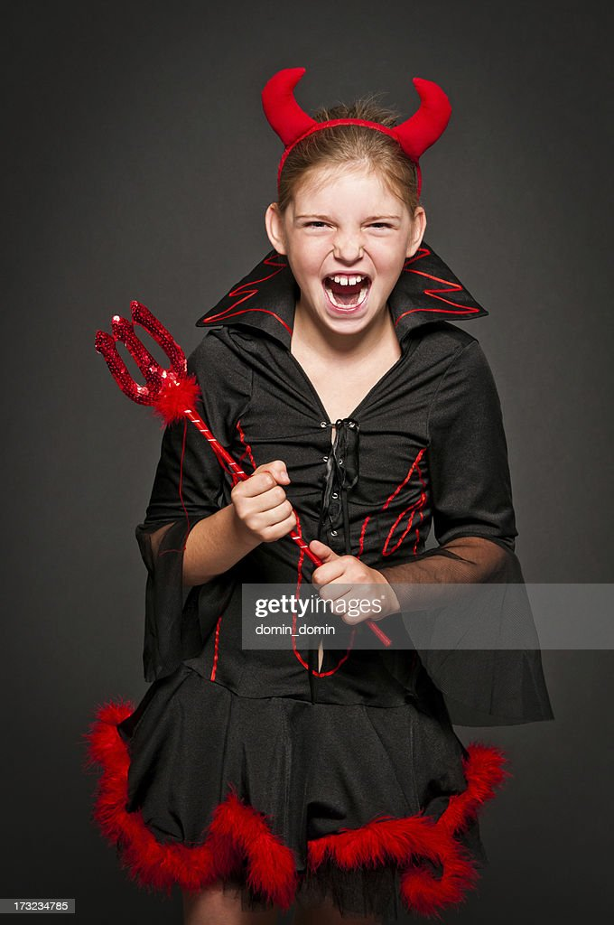 Girl in devil costume laughing and screaming, isolated on black : Stock Photo