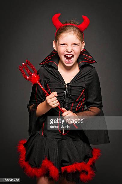 girl in devil costume laughing and screaming, isolated on black - devil costume stock photos and pictures