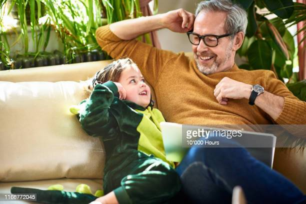 girl in dinosaur costume smiling at mature father on sofa - retirement stock pictures, royalty-free photos & images