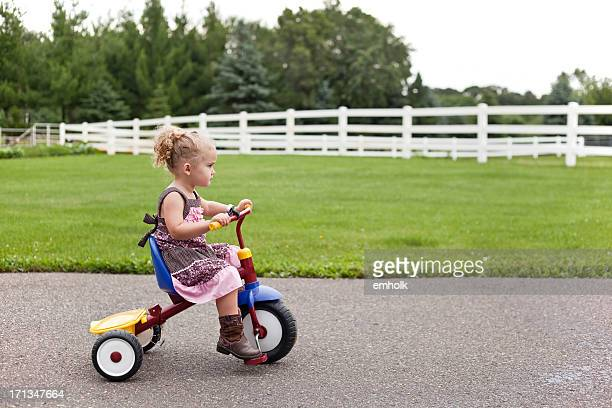 girl in dress & cowboy boots riding tricycle - cowgirl hairstyles stock photos and pictures