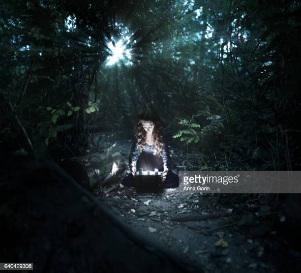 Girl in dress kneels on forest path at night, opening box with light illuminating her