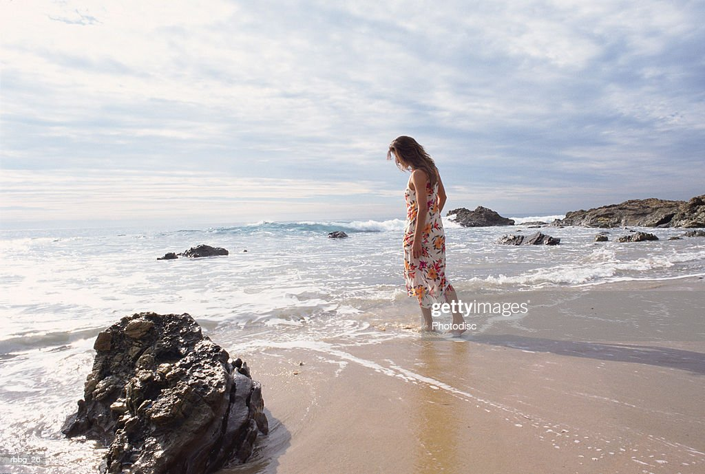 Girl in dress walking along the beach on a cloudy afternoon : Stockfoto