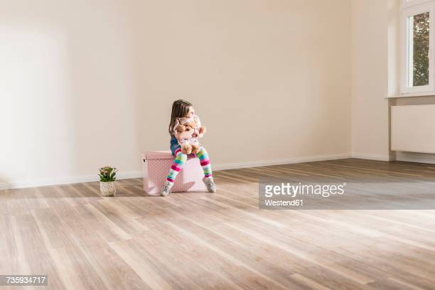 girl in empty apartment holding teddy - toy box stock pictures, royalty-free photos & images