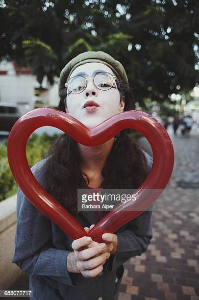 A girl in face paint with a heartshaped balloon in Oahu Hawaii February 1994