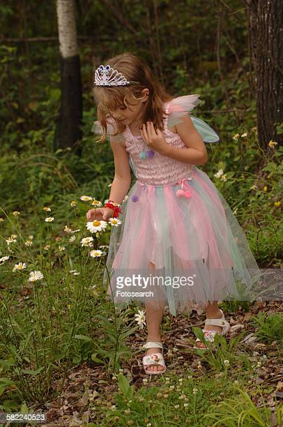 Girl in fairy costume picking wildflowers