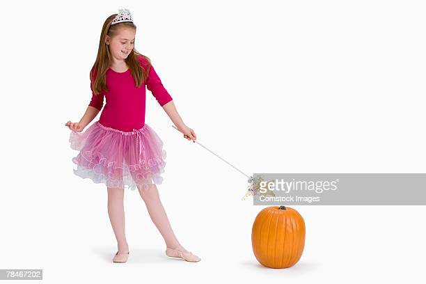 Girl in fairy costume pointing magic wand at pumpkin
