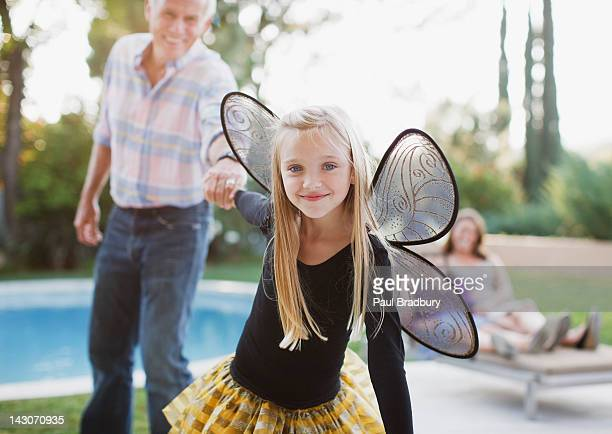 Girl in fairy wings pulling grandfather along