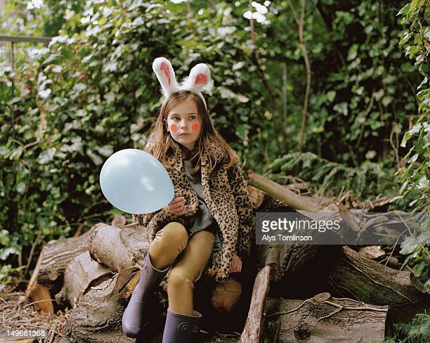 Girl in fancy dress holding a ballon outdoors