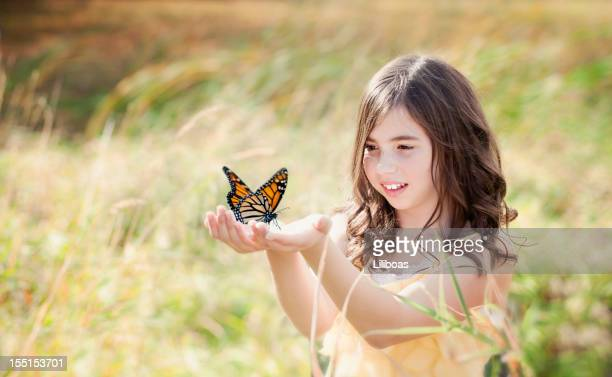 Girl in Field Holding a Monarch Butterfly