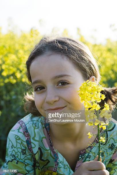 Girl in field of yellow flowers, holding up blossom, portrait