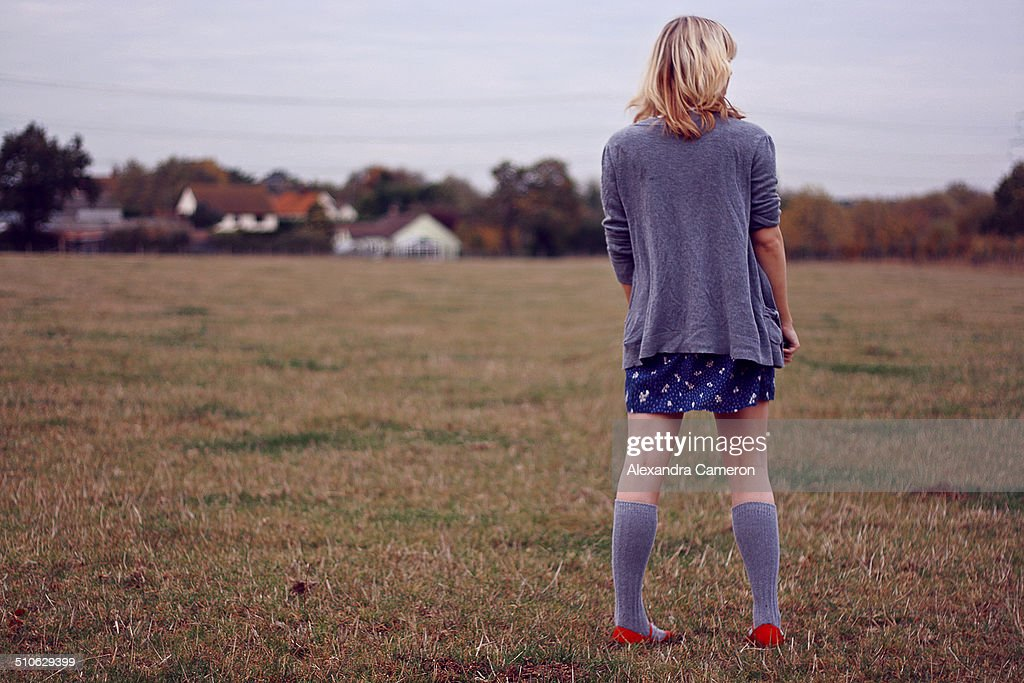 Girl in field with red shoes : Stock Photo