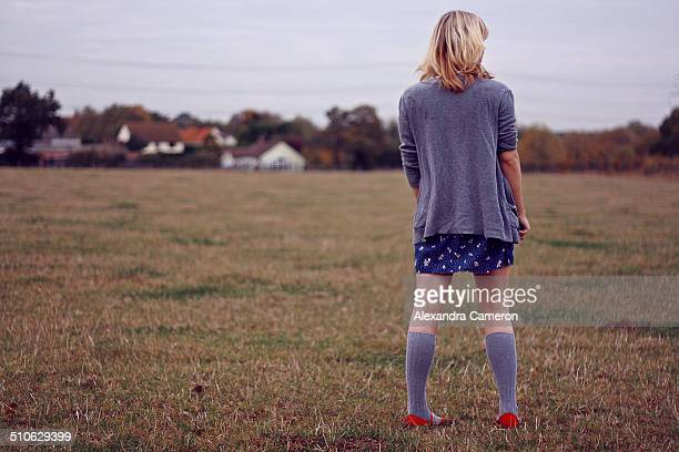 girl in field with red shoes - little girls up skirt stock pictures, royalty-free photos & images