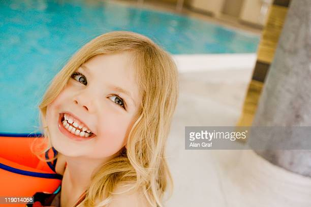 Girl in floaters by swimming pool
