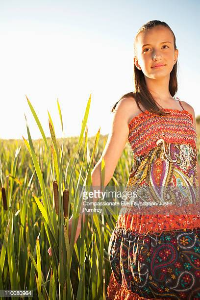 "girl in floral dress standing in tall grass - ""compassionate eye"" fotografías e imágenes de stock"
