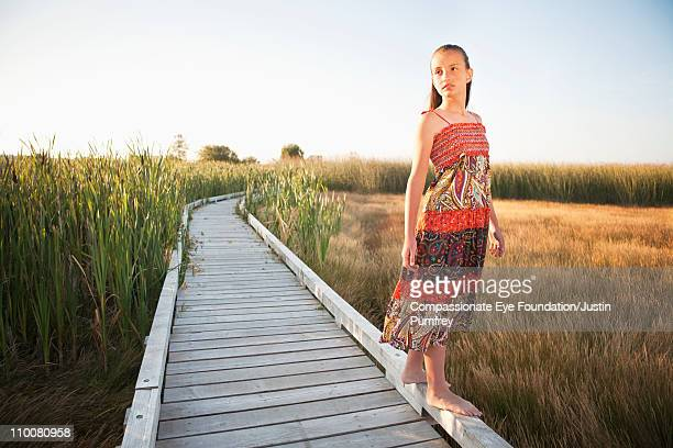 "girl in floral dress standing on a walkway - ""compassionate eye"" stock-fotos und bilder"