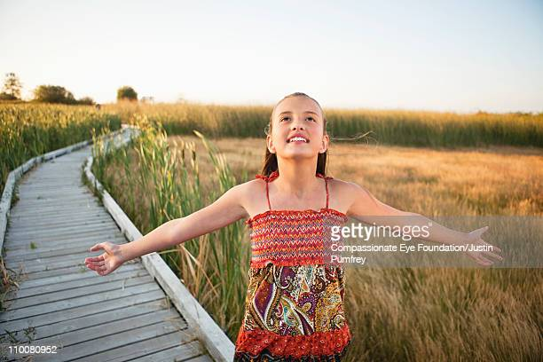 "girl in floral dress standing with open arms - ""compassionate eye"" fotografías e imágenes de stock"