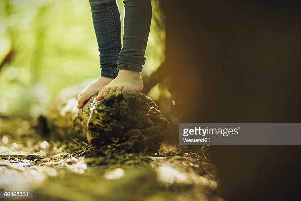 Girl in forest standing on log
